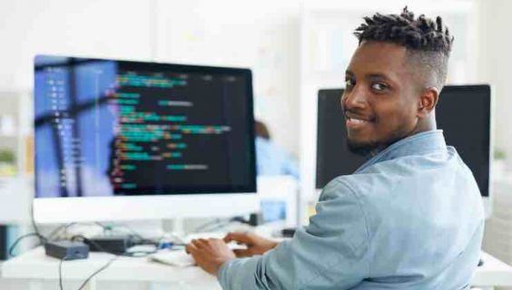 Smiling black guy looking over his shoulder at you while working in front of a computer