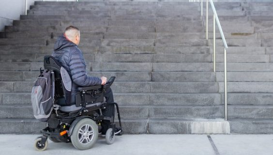 A man in a powered wheelchair at the foot of a steep concrete staircase