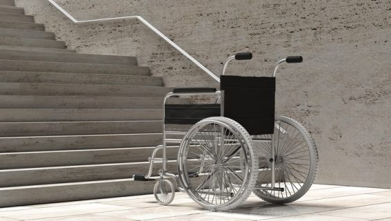 An empty wheelchair at the foot of a steep flight of concrete stairs