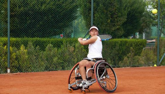 A woman in a wheelchair getting ready to return a fast serve on a tennis court