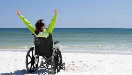 Woman in a wheelchair staring out at the surf