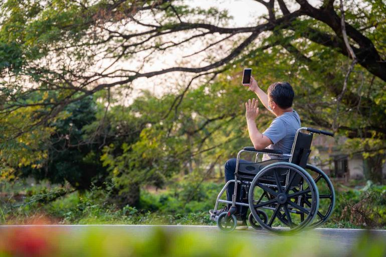 An Asian man in a manual wheelchair, takes a photo with his smartphone up through the branches of a large tree.