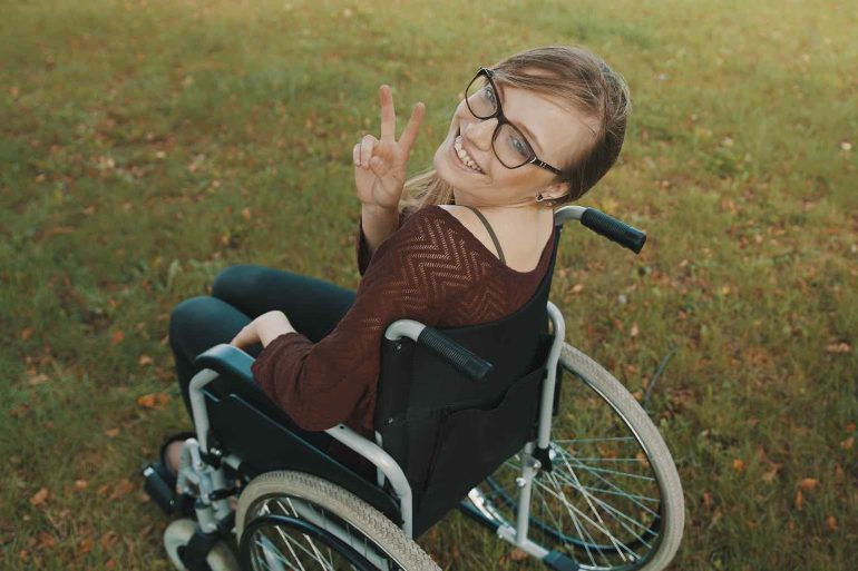 Beautiful disabled caucasian woman looking over the shoulder in the park, peace gesture.