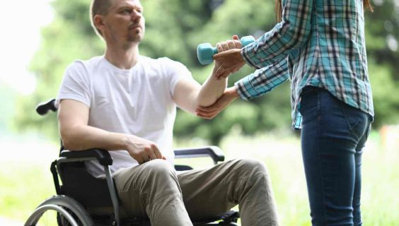 Close-up of middle-aged man sitting in wheelchair and trying to exercise with blue dumbbell. Woman helping male training arm. Sport and active lifestyle.