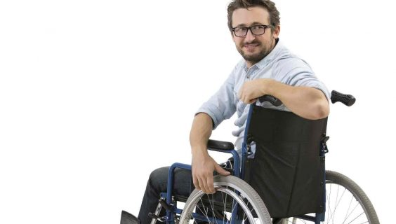 Young Man sitting on a wheelchair looks back after be called