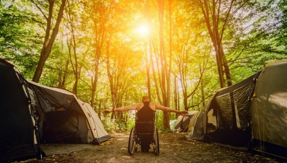 A man in a wheelchair in a campsite n a dense pristine woodland spot with his arm flung wide, as a golden defuse sun beams down