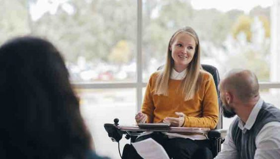 A young happy woman in a wheelchair speaking to a workshop