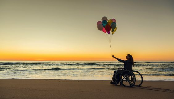 A woman in a wheelchair, on the beach, holding a few balloons