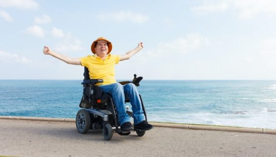 Man in powered wheelchair by the beach, arms spread wide in joy