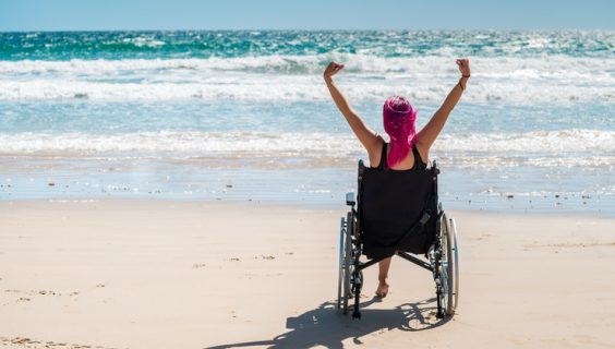 Woman in a wheelchair stares out to the surf with her arms raised