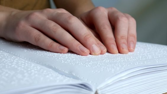 Two male hands 'reading' a braille book