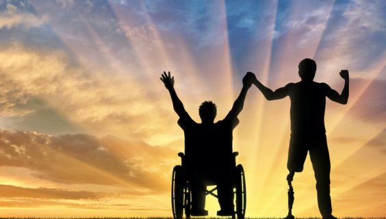 A man in a wheelchair and a man with an artificial leg greet the dawn with enthusiasm