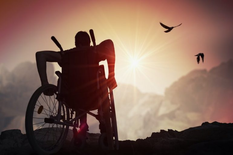 Man on a wheelchair, rolling up to a bright vista