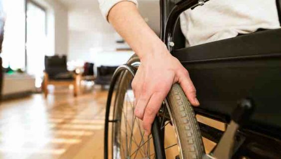 A woman in a wheelchair rests her hand on her wheel