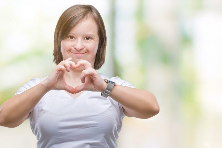 Smiling young woman make a heart symbol with her hands
