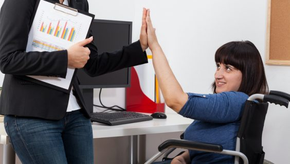 Woman in a wheelchair high-fiving a business woman with a folder