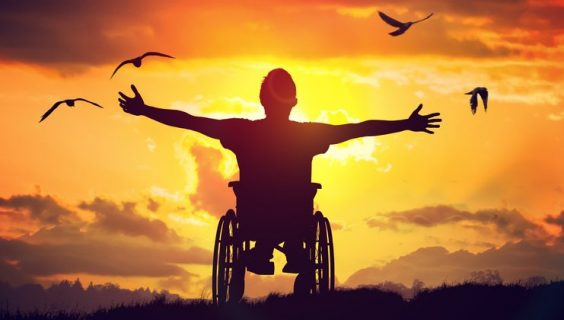 A man in a wheelchair throws his arms wide to greet the morning sun.