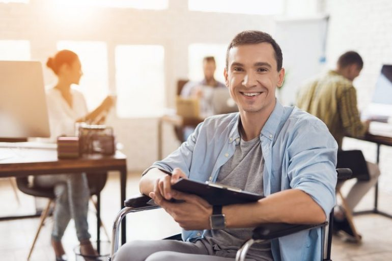 Smiling man in a wheelchair in a busy office