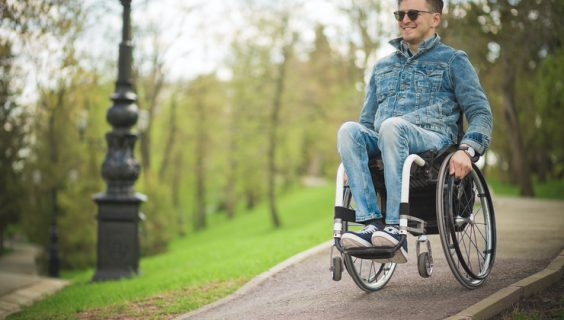 Smiling man in a wheelchair with sunglasses coasts down a park's pathway