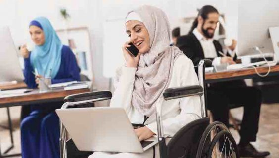 A woman wearing a hijab in a wheelchair talking on a mobile phone