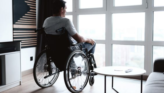 A man in a wheelchair looks out through a wall of windows pondering.