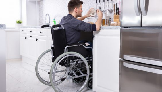 Man in a wheelchair preparing food on a modified kitchen bench.
