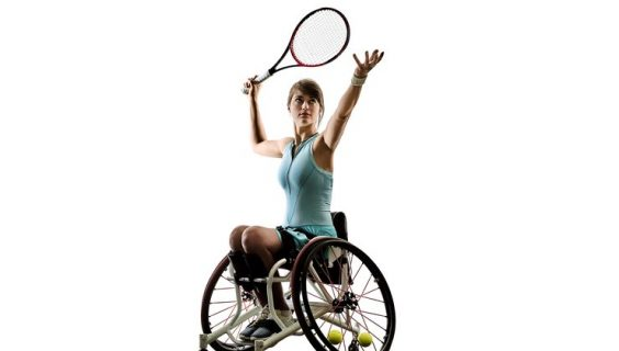 A woman in a wheelchair in the process of a tennis serve