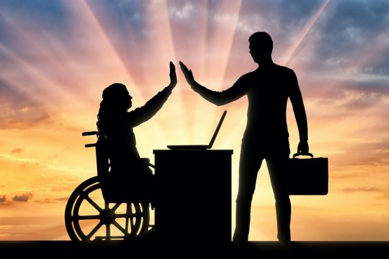 Silhouette of a woman in a wheelchair and a standing man with a briefcase high five over a desk and laptop
