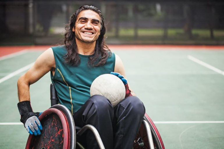 Grinning sporting wheelie on a court