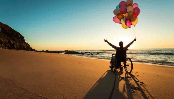 A woman in a wheelchair, celebrates with baloons beside the sea