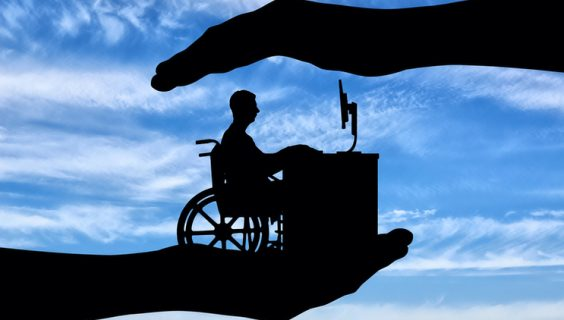 Silhouette of a man in a wheelchair at a workstation