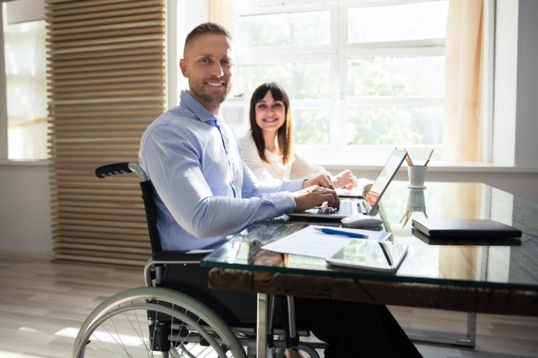 wheelchair and woman looking up smiling from working beside.